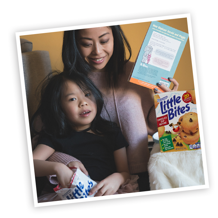 Mother and child with Little Bites Chocolate Chip muffins package